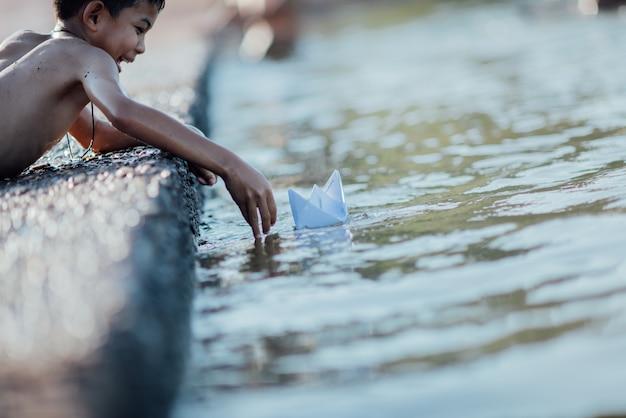Asiatischer junge, der papierboot im fluss spielt