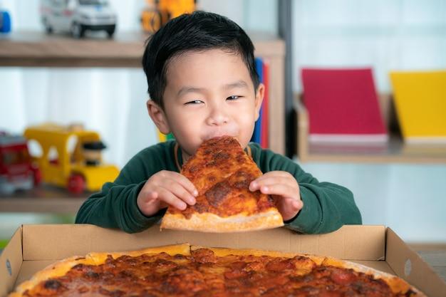 Asiatischer junge, der pizza und pizzaschachtel isst, legte auf den tisch.