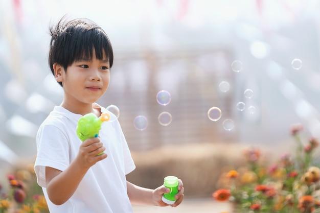 Asiatischer junge, der seifenblasen bläst