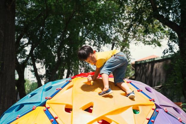 Asiatischer junge, der spaß hat, auf dem kletterspielzeug für kinder auf dem schulhof zu spielen, zurück zu den aktivitäten im freien