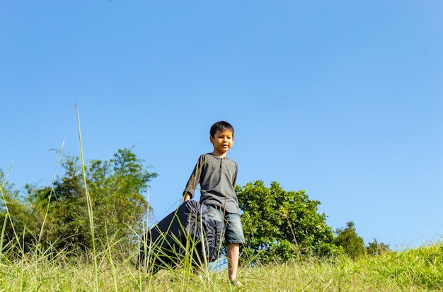 Asiatischer junge, der tasche hintergrundgras und -bäume hält.