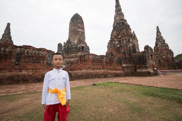 Asiatischer junge, der thailändisches kleid im alten tempel trägt