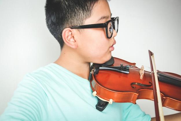 Asiatischer junge, der violineninstrument spielt