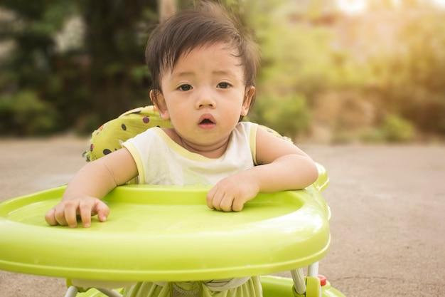 Asiatischer junge der weichzeichnung, der auf einem babystuhl sitzt