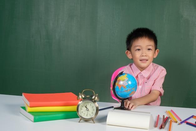 Asiatischer junge, der weltkarte im kreidebrettraum zeigt