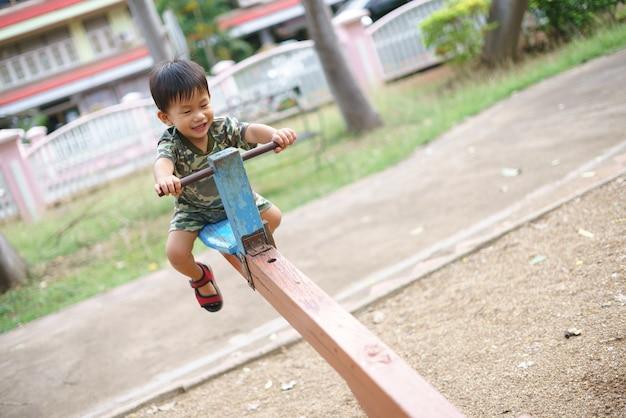 Asiatischer junge, der wippen spielt und spaß mit seiner mutter am kindertrainingsspielplatz hat