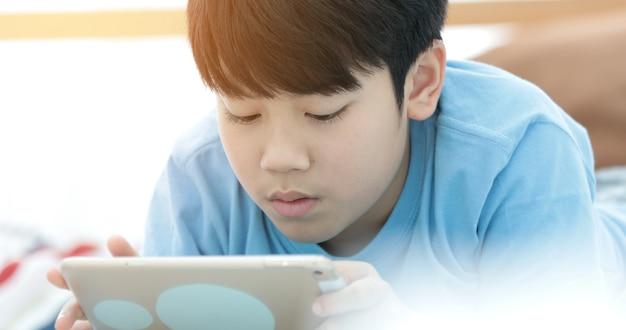 Asiatischer junge, der zu hause spiel auf digital-tablet liegt und spielt