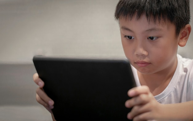 Asiatischer junge, der zu hause spiel auf digitaler tablette, kinder aufpassen karikaturen auf digitalem taplet oder smartphone spielt
