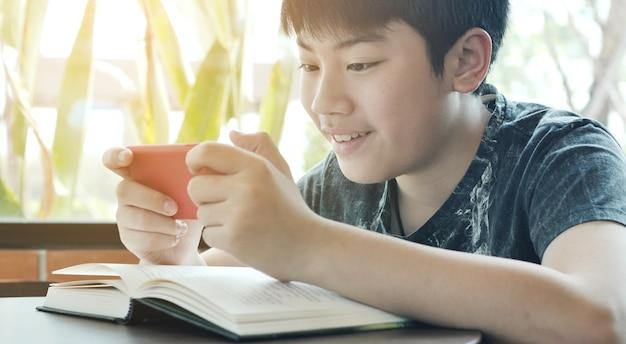 Asiatischer junge, der zusammen bewegliches spiel am intelligenten telefon spielt.