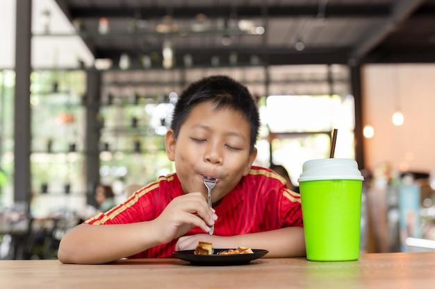Asiatischer junge des glücklichen gesichtes genießen, schokoladenwaffel im restaurant zu essen.
