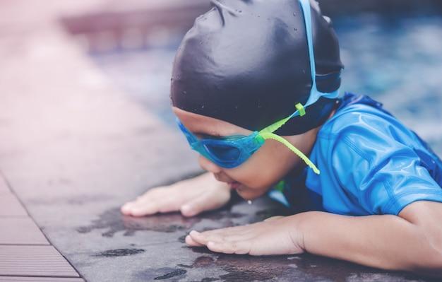 Asiatischer junge des nassen anzugs mit schwimmengläsern ist schwimmen in einem pool