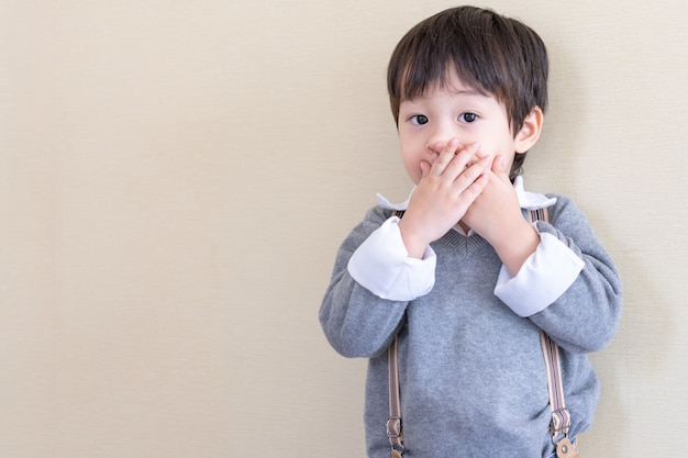 Asiatischer junge des porträts, der steht und schloss seinen mund