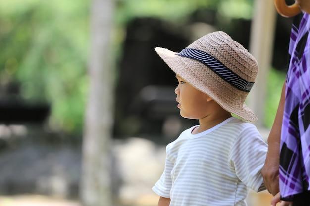 Asiatischer junge hat interessen während im zoo.