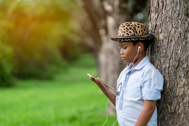 Asiatischer junge hört musik unter verwendung der kopfhörer mit einem smartphone am park.