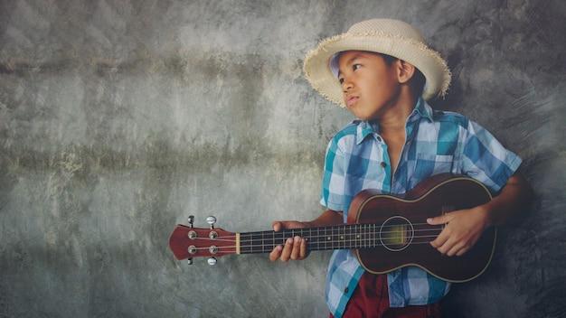 Asiatischer junge im alter von 5-6 spielen ukulele coole geste leidenschaftliche liebe im leeren musikraum