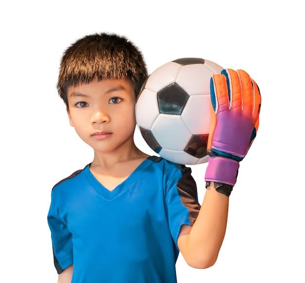 Asiatischer junge ist ein fußballtorhüter, der handschuhe trägt und einen fußball hält, der auf weiß isoliert wird.