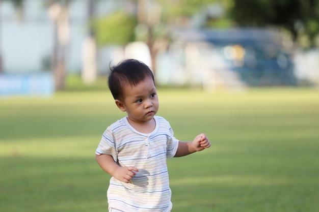 Asiatischer junge lernt im garten laufen.