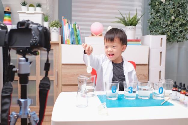 Asiatischer junge macht chemieexperimente und nimmt ein video für seine anhänger auf, junges bloggerkind posiert vor der kamera, kinder machen vlog für social-media-kanal-konzept
