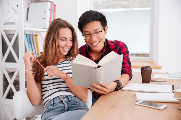 Asiatischer junge mit brille und hemd in einem käfig und frau in t-shirt in einem streifendruck, die zusammen für ein projekt arbeiten, während sie im klassenzimmer sitzen?