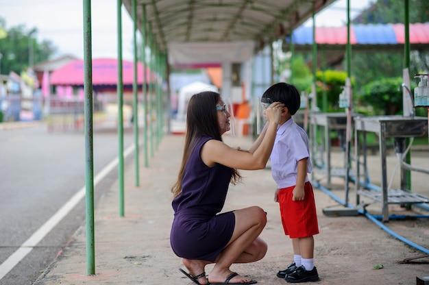 Asiatischer junge mit mutter, die gesichtsschutzmaske zum schutz vor covid-19 trägt