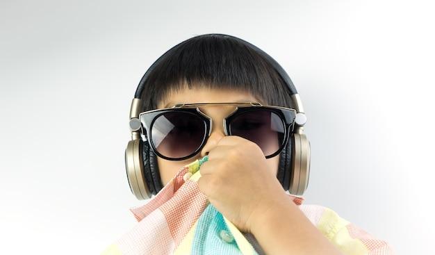 Asiatischer junge mit sonnenbrille hört musik auf kopfhörer