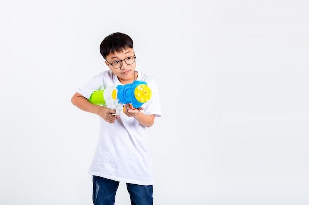 Asiatischer junge mit spritzpistole auf weißem hintergrund