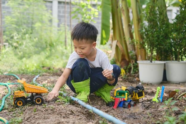 Asiatischer junge mit stiefeln, der in schlammigen pfützen spielt und zu hause mit spielzeug-lkw in schlammigem boden gräbt
