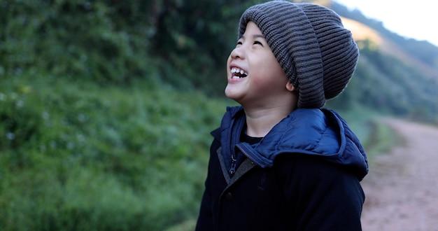 Asiatischer junge mit wollmütze und lachen in der wintersaison