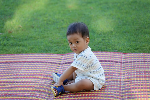 Asiatischer junge sitzt im garten.