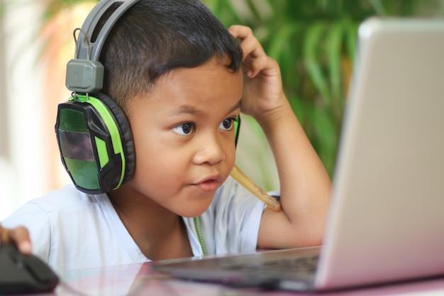 Asiatischer junge sitzt mit laptop am tisch und bereitet sich auf die schule vor. online-bildungskonzept. online-videoanruf-konferenz-unterrichtsunterricht.