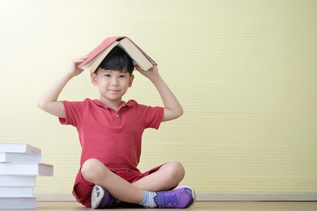 Asiatischer junge sitzt und hat ein buch auf seinem kopf. lernkonzept für kinder.