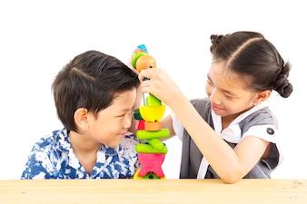 Asiatischer Junge und Mädchen spielen glücklich buntes hölzernes Blockspielzeug