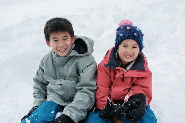 Asiatischer junge und mädchen der glücklichen mischrasse, geschwister, die auf weißem schnee in japan lächeln und sitzen