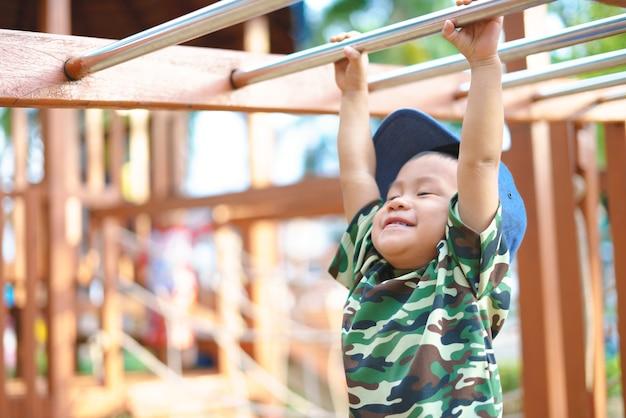 Asiatischer junge ungefähr 1 jahr und 9 monate in der militärklage, die am kindertrainingsspielplatz spielt