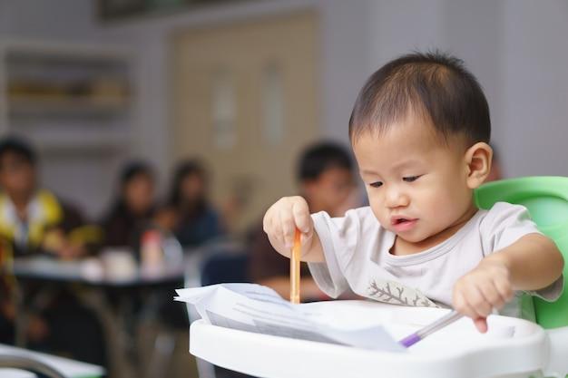 Asiatischer junge ungefähr 1 jahr und ein monatslernen schreiben mit stift und papier