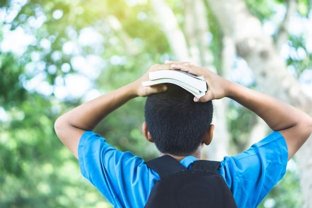 Asiatischer jungenstudent, der zur schule hält bücher auf kopf geht