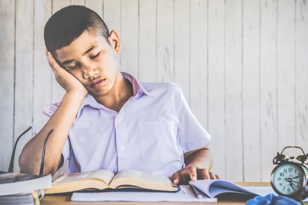 Asiatischer jungenstudent ermüdete vom in der schule studieren