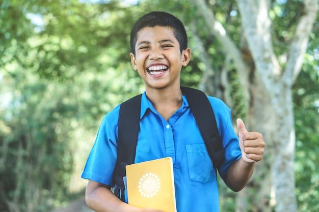 Asiatischer jungenstudent zurück zu der schule, die über einen park lacht