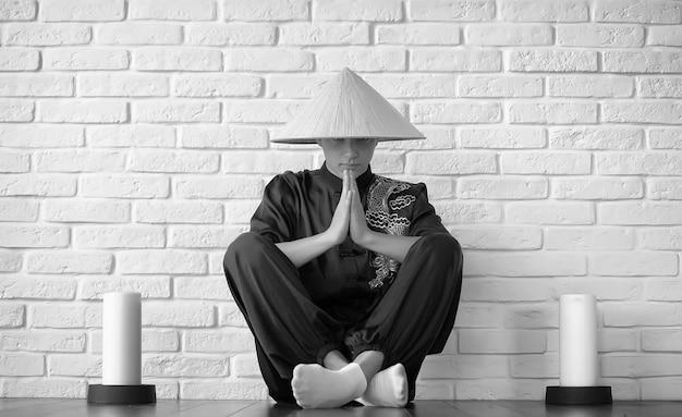 Asiatischer junger anfänger auf einem weißen backsteinmauerhintergrund