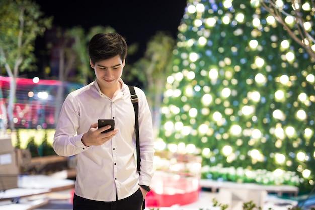 Asiatischer junger attraktiver geschäftsmann, der smartphone verwendet