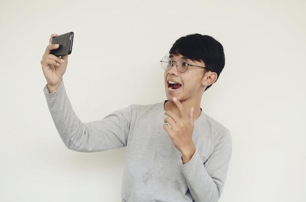 Asiatischer junger attraktiver mann mit smartphone macht ein selfie-foto