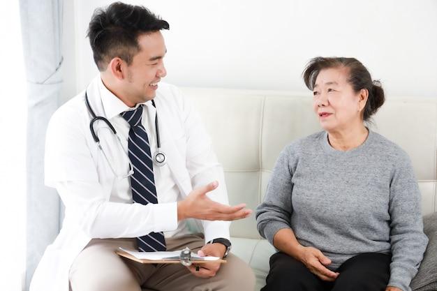 Asiatischer junger doktor, der mit älterer frau im krankenhaus spricht