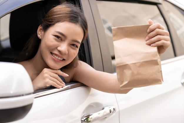 Asiatischer junger erwachsener im auto, das einwegbeutel für herausgenommenes essen vom durchfahrtsrestaurant hält. drive thru ist ein neuer normaler und beliebter dienst nach einer coronavirus-covid-19-pandemie.