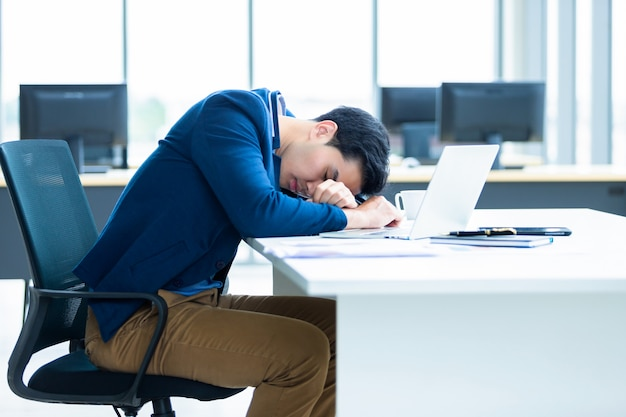 Asiatischer junger geschäftsmann arbeitete spät und schlief auf einem laptop im büroraum ein