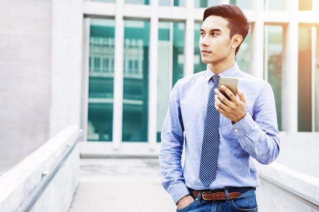 Asiatischer junger geschäftsmann benutzen ein intelligentes telefon und schauen vorwärts