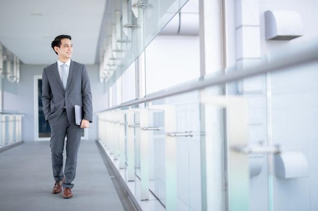 Asiatischer junger geschäftsmann im flughafen. lässiger städtischer professioneller geschäftsmann, der smartphone glücklich innerhalb des bürogebäudes oder des flughafens lächelt. hübscher mann, der anzugjacke drinnen trägt.