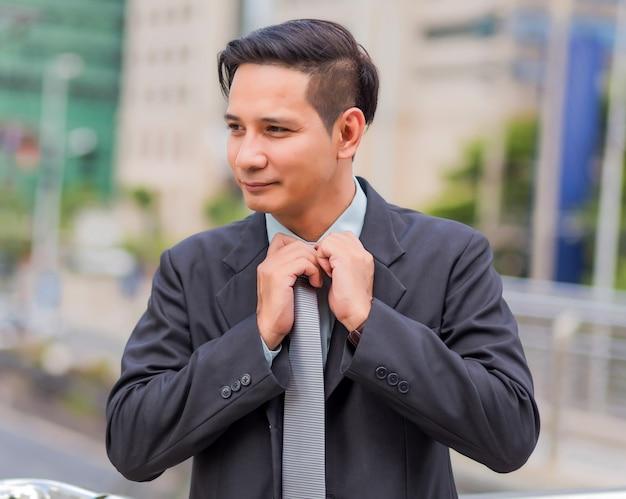 Asiatischer junger geschäftsmann vor dem modernen gebäude in der innenstadt. konzept der jungen geschäftsleute