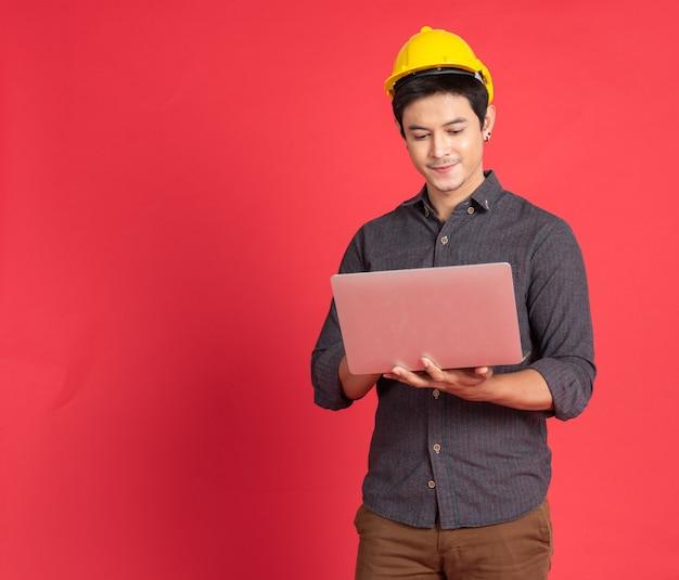 Asiatischer junger ingenieurmann halten laptop
