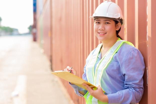 Asiatischer junger jugendlicher glücklicher arbeiter, der lagerbestand in der schifffahrtshafenarbeit prüft, verwaltet import-exportfrachtcontainer.