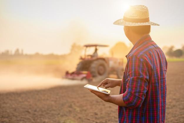 Asiatischer junger landwirt, der auf dem gebiet arbeitet